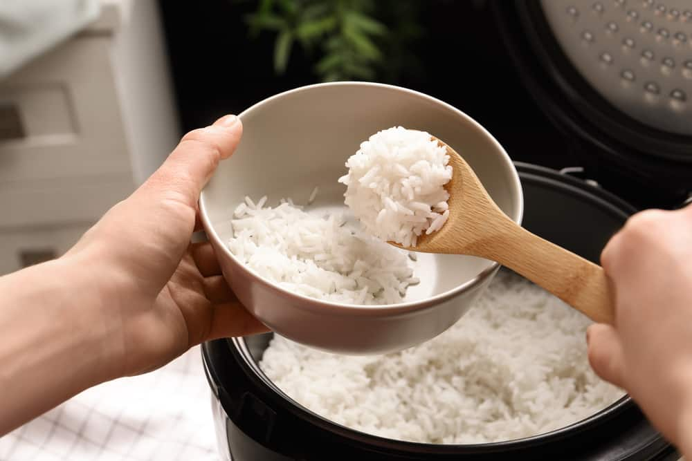 Woman putting tasty rice into bowl from cooker in kitchen, closeup